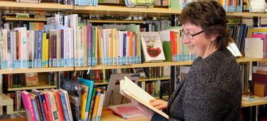 Pfarrbücherei Burgau Innenansicht mit Frau lesend