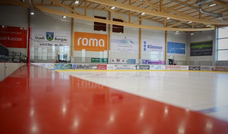 Blick auf die Eisfläche der Städtischen Eissporthalle Burgau. Der Blick führt dabei entlang der roten oberen Bandenkante bis hin zur anderen Seite der Eisfläche. Die Kamera wurde beim Fotografieren direkt auf diesen roten Handlauf gelegt.