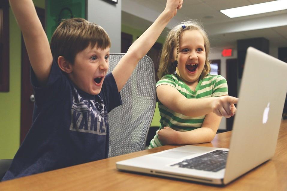 Kinder die jubelnd vor einem Laptop sitzen