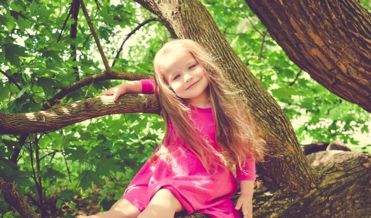 Ein Mädchen sitzt lachend auf einem Baum