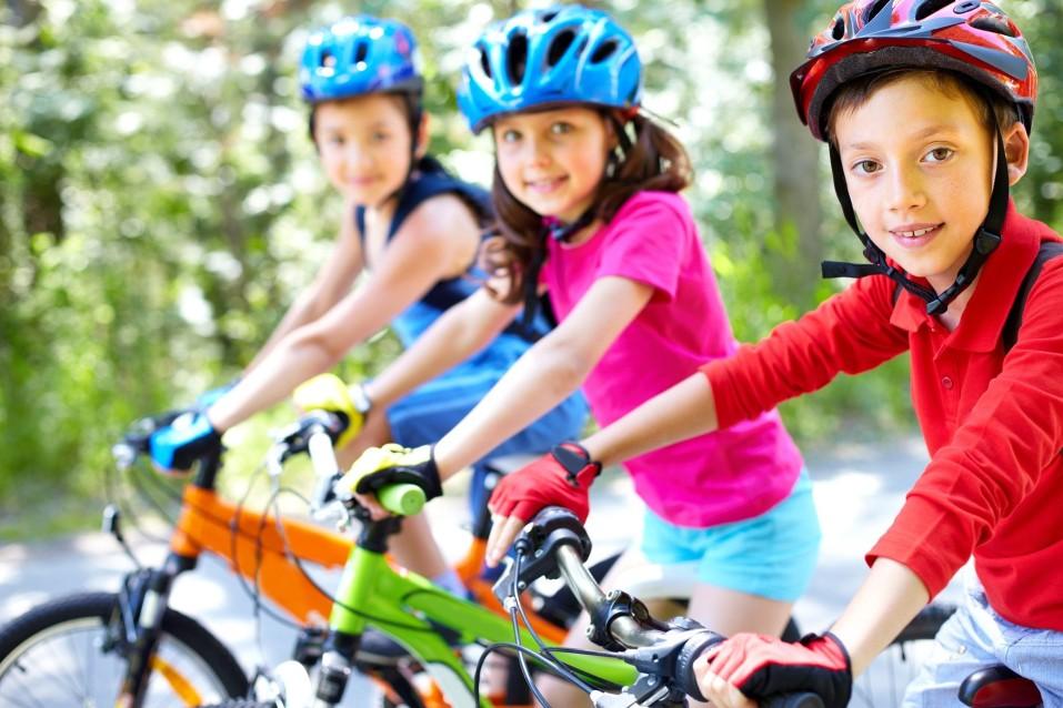 Drei Kinder, die auf ihren Fahrrädern sitzen und lachen